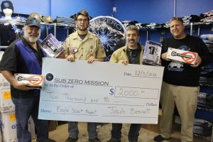 Jacob Bennett presents the check the went towards the purchase of equipment